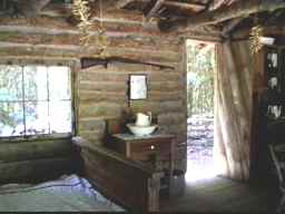 cabin interior: bed and long gun on wall